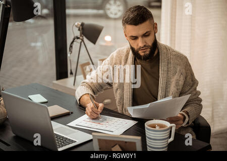 Confused self-employed bearded man flipping through papers - Stock Photo