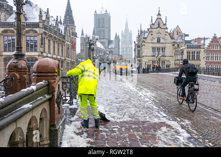 Cyclist on slippery road and city worker cleaning pavement during sleet / snow shower in winter in the city Ghent, East Flanders, Belgium - Stock Photo
