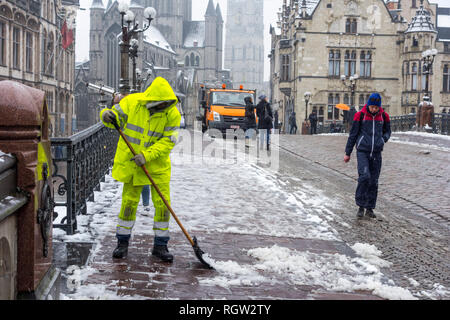 Pedestrians on slippery road and city worker cleaning pavement during sleet / snow shower in winter in the city Ghent, East Flanders, Belgium - Stock Photo