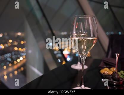 Glass of white wine on a black table in restaurant. Night city lights bokeh through panoramic windows in the background. Recreation in luxury place - Stock Photo