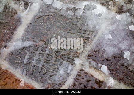 Footprints of pedestrian in wet snow / sleet on slippery pavement / dangerous sidewalk in winter - Stock Photo