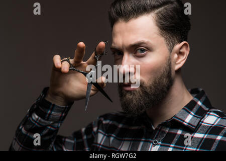 Young handsome bearded man with long beard moustache and brunette hair holding hairdresser or barber scissors with emotional face in studio on grey ba - Stock Photo