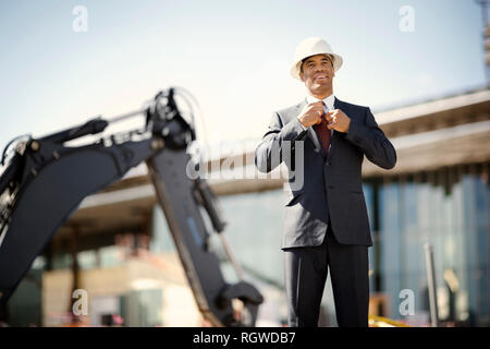 Young engineer wearing a suit and hardhat adjusts his tie while standing in front of a digger at a construction site. - Stock Photo