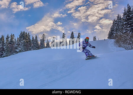 Young man snowboarder running down the slope in Karakol mountains - Stock Photo