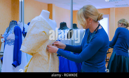 Professional tailor, designer working with new model tailoring dress on mannequin in studio, atelier. Fashion and tailoring concept - Stock Photo