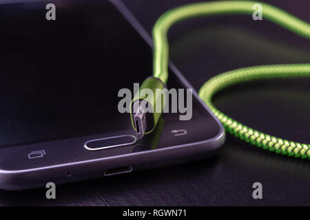 A usb cable for data transfer and phone charging. Telephone and accessories on the table. Dark background. - Stock Photo
