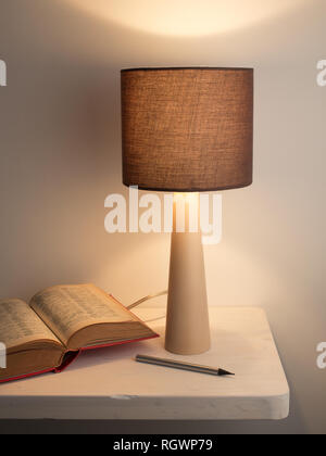 Learning languages concept. Night lamp and book on the white desk or nightstand. White background - Stock Photo