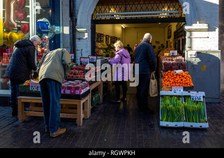 Customers at a greengrocer and fruiterers shop in an Archway in Middlesbrough Town Centre - Stock Photo