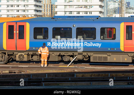 Clapham Junction, UK; 30th January 2019; South Western Railway Employee in Orange Hi Visibility Safety Clothing Stands in Front of Passing Train - Stock Photo