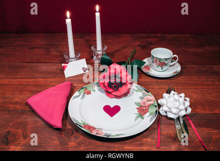 Floral pattern fine china dinnerware with matching plate, cup and saucer. pink rose, pink napkin, silverware, white candles and card - Stock Photo