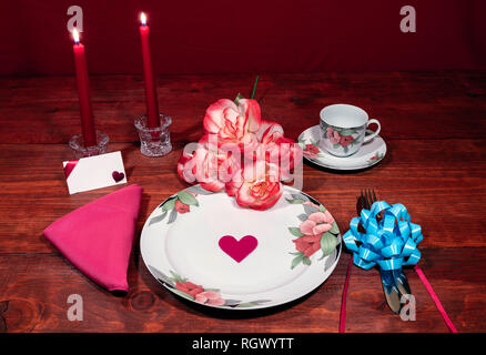 Floral pattern fine china dinnerware with matching plate, cup and saucer. bouquet of orange and white rpses, pink napkin, silverware, red candles and  - Stock Photo