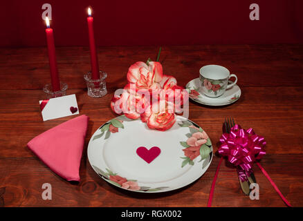 Floral pattern fine china dinnerware with matching plate, cup and saucer. bouquet of orange and white roses, pink napkin, silverware, red candles and  - Stock Photo