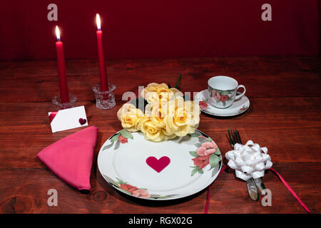 Floral pattern fine china dinnerware with matching plate, cup and saucer. bouquet of yellow roses, pink napkin, silverware, red candles and card - Stock Photo