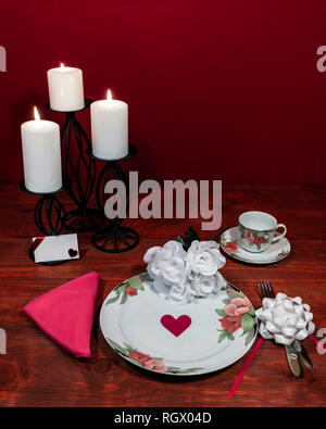 Floral pattern fine china dinnerware with matching plate, cup and saucer. bouquet of white roses, pink napkin, silverware, white candles and card - Stock Photo