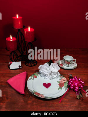 Floral pattern fine china dinnerware with matching plate, cup and saucer. bouquet of white roses, pink napkin, silverware, red candles and card - Stock Photo