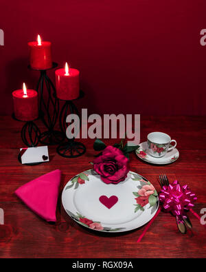 Floral pattern fine china dinnerware with matching plate, cup and saucer. pink rose, pink napkin, silverware, red candles and card - Stock Photo