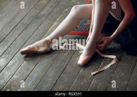 Ballerina prepare to performance. Young beautiful woman ballet dancer, dressed in professional outfit, pointe shoes and black tutu. - Stock Photo