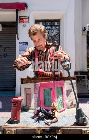 Street performer with a puppet, or marionette, during the San Telmo district Sunday market in Buenos Aires, Argentina. - Stock Photo