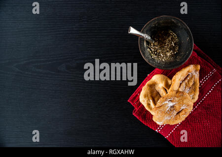 Latinamerican culture: Mate infusion and torta frita over a dark background. - Stock Photo
