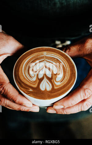 A cup of coffee with a heart latte foam art on top, being helf by masculine hands, warm brown colors, earth tones. - Stock Photo