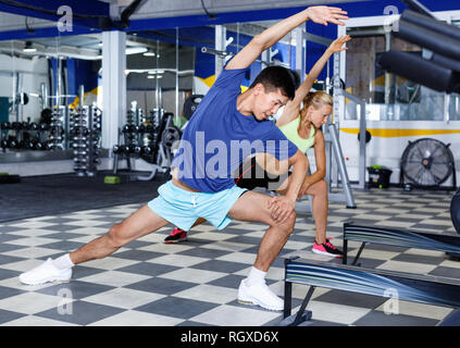 Portrait of young glad cheerful positive smiling athletic couple practicing stretch exercises in fitness center - Stock Photo