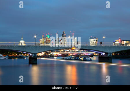 View down the River Thames at dusk to Waterloo Bridge and beyond to St Paul's Cathedral and the City of London, UK - Stock Photo