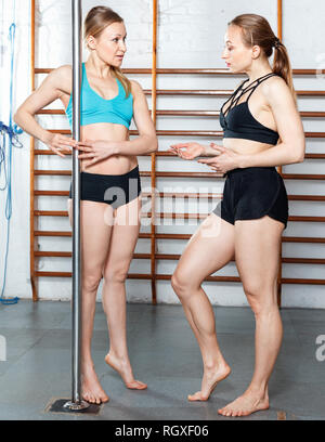 Two glad positive  slim girls discussing their bodies during training in fitness gym - Stock Photo