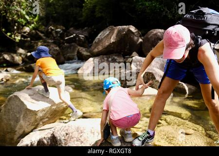 A family crossing a stream during a hike, Finch Hatton, Queensland 4756, Australia - Stock Photo