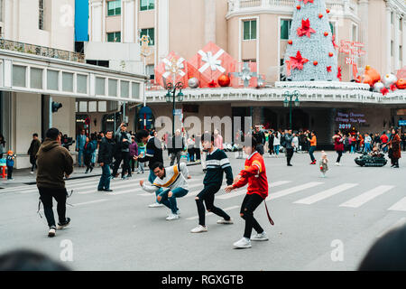 Hanoi, Vietnam, 12.20.18: Life in the street in Hanoi. Boyband films their music video in the middle of the street. - Stock Photo