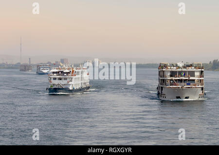 Tourist boats on the Nile river near Aswan. A fleet of floating hotels (tourist boats) motor down the River Nile towards Aswan in central Egypt. The t - Stock Photo