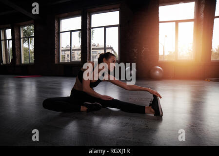 Athletic girl does stretching exercises at the gym - Stock Photo