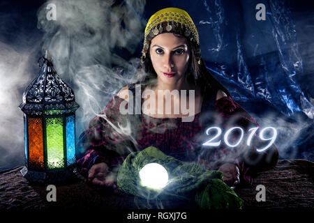 Female fortune teller or psychic reading with a cystal ball predicting the future of the year 2019 - Stock Photo
