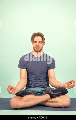 Man meditate on yoga mat. Sportsman relax in lotus pose. Fashion athlete practice yoga in gym. Meditation for body and mind health. Meditation or zen and peace concept. - Stock Photo