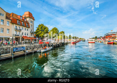Tourists enjoy the shops, boats and cafes on the Alter Strom canal boardwalk in the town of Warnemunde, Rostock on the northern coast of Germany - Stock Photo