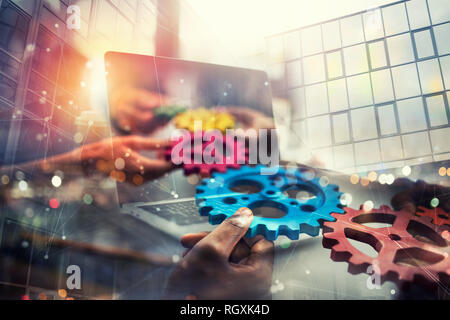 Business people with gears in hand that exit from a laptop. concept of remote cooperation and teamwork. Double exposure