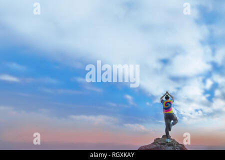 Minimalist of a man wearing a variety of bright colors stand acts like trees on the rock and the sky is beautiful. This photo contain noise and burry. - Stock Photo