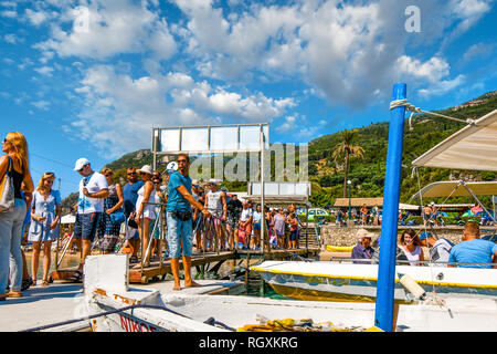 Corfu, Greece - September 20 2018: A tour boat leader maintains the boats in dock as tourists line up at Palaiokastritsa Beach on the island of Corfu - Stock Photo