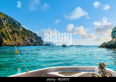 A small boat heads towards other boats and out of the Palaiokastritsa  bay towards the Aegean Sea on the Island of Corfu Greece. - Stock Photo
