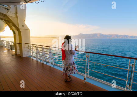A woman sips a drink on the deck of a cruise ship as the sun sets and the ship passes islands on the Aegean Sea - Stock Photo
