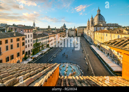 Rome, Italy - September 30 2018: Early morning view from a terrace overlooking Piazza Navona as sunlight lights the dome on the St. Agnes Cathedral - Stock Photo