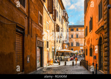 Rome, Italy - September 30 2018: A woman walks through an empty alley towards a sidewalk cafe and small piazza in the historic center of Rome, Italy - Stock Photo