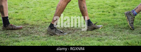 Close up photo of boys legs and sneakers covered in mud after a cross country meet. - Stock Photo