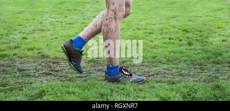 Close up photo of a boy's legs and sneakers covered in mud after a cross country meet. - Stock Photo