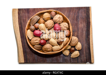 Mixed nuts in wooden bowl on piece of exotic Cola Bola wood - Stock Photo