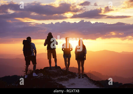 Group of four tourists or friends stands on mountain top and looks at sunset. Peoples travel concept - Stock Photo