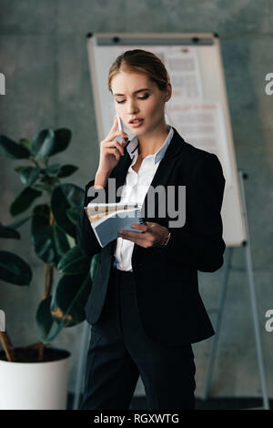 Young businesswoman seriously talking on smartphone while holding notebooks in hands - Stock Photo