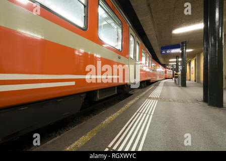Train Station at Night with a Orange Train in Lugano, Switzerland. - Stock Photo