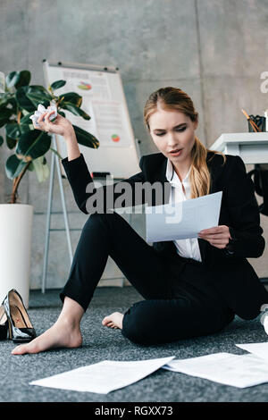 shocked businesswoman reading document and sitting barefoot on floor