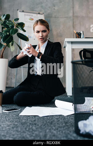 businesswoman sitting on floor and throwing crumpled papers to basket - Stock Photo