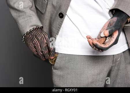 cropped shot of tattooed man in suit holding coins and putting bitcoin in pocket isolated on grey - Stock Photo